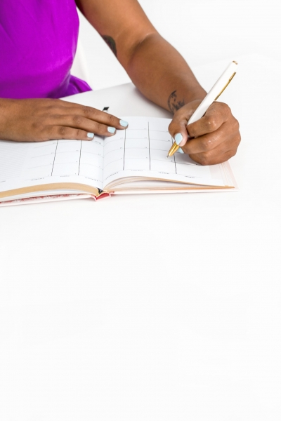 Black girl writing with a pen in a planner
