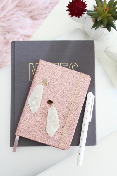 grey book with a sparkly pink planner on top and white feather earrings
