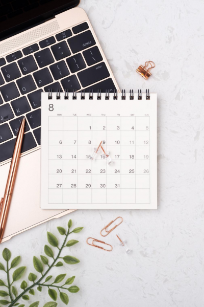 rose gold laptop with a rose gold pen and calendar on top