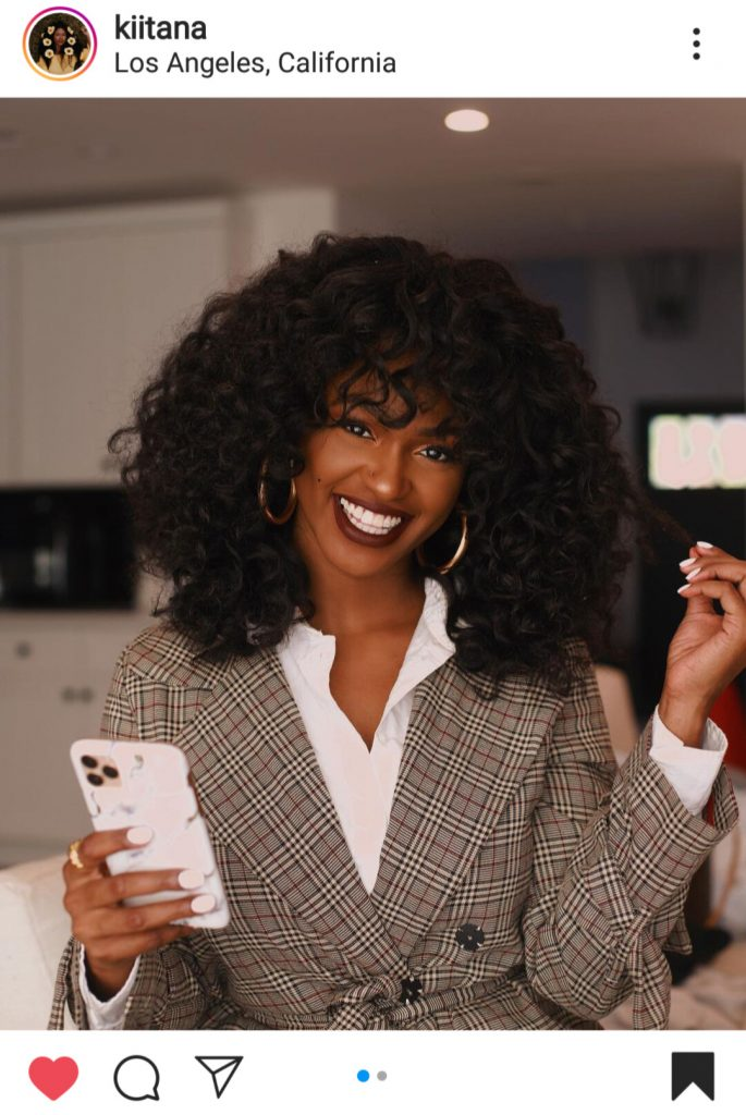 Photo is a picture of Kiitana on instagram. She is wearing a white button up with a plaid jacket over it. She has a phone in her hand and is wearing a natural  fall makeup look with a red lip color. She is smiling bright.