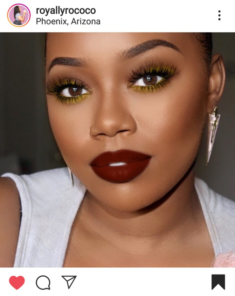 A close up face photo of royallyrococo on instagram. She is wearing a fall makeup look with yellow liner lined at the bottom of her eyes. She also is wearing a deep red lipstick.