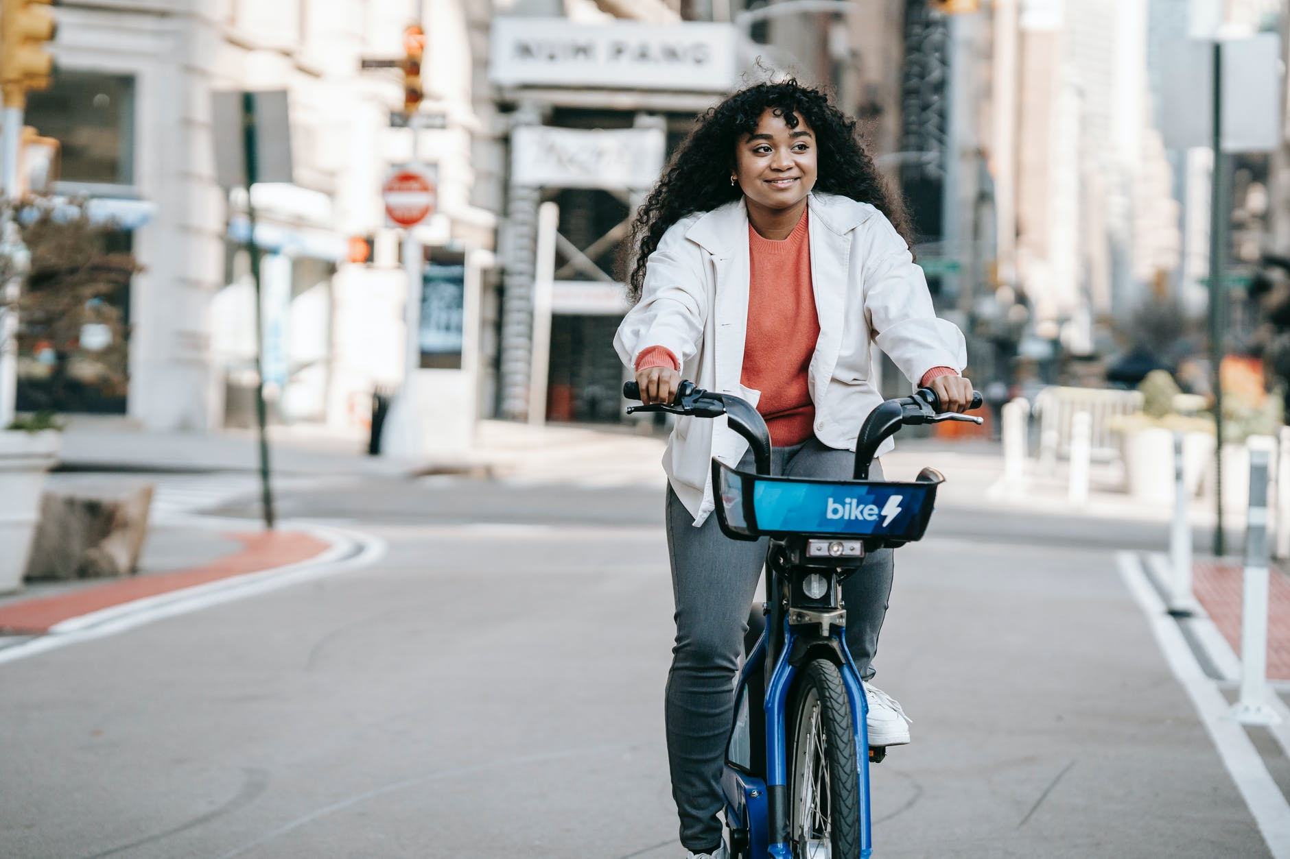 cheerful black woman riding bicycle on street